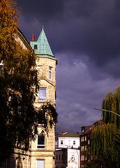 Gebäude mit Spitzdach vor bedrohlichen Regenwolken