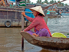 Market-woman steering her boat on the Hậu Giang river