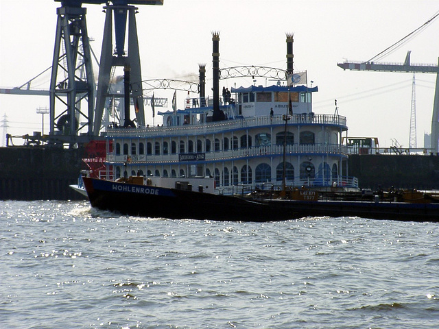 "Paddle wheel steamer ""Louisana Star"" in front of cranes"
