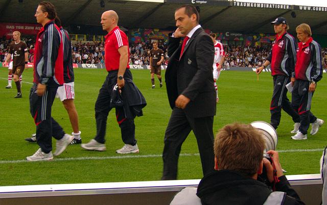 Mit Anzug auf Fussballfeld herumstolzierende Leute...