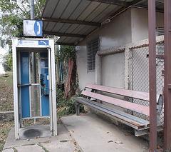 Phone booth and long rustic bench / Banc rustique et cabine téléphonique.
