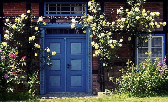 Tür im Fachwerkhaus mit Rosensträuchern