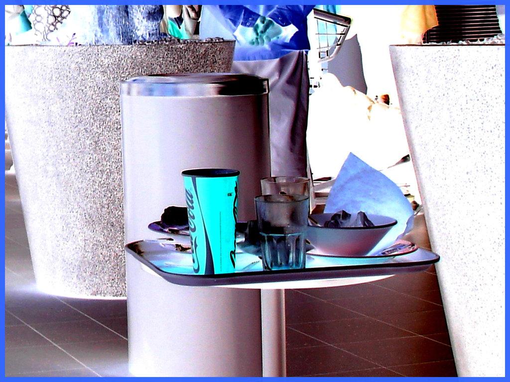 Coca-cola and water leftovers -  Plateau collation à la Coca-cola - Schiphol airport- Photofiltré en négatif.