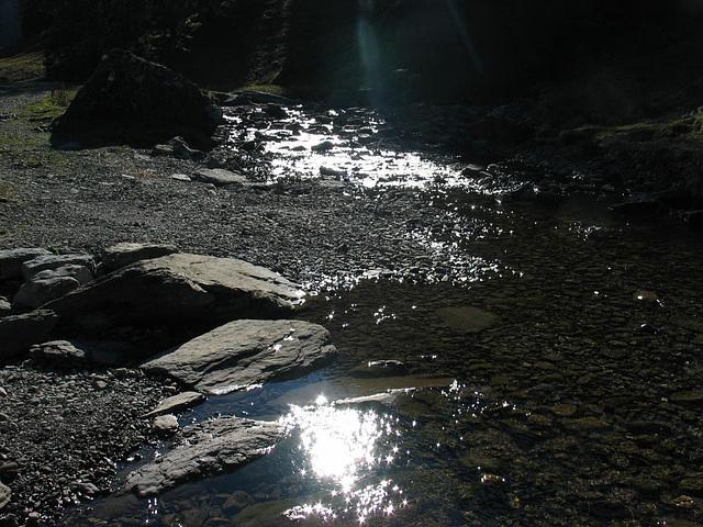 Glitzerndes Sonnenlicht im Bergbach