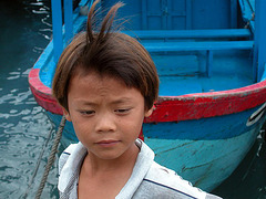 A boy arranges the wharfs for the fishing boats