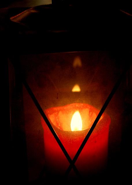 Flameto de ruĝa kandelo en lanterno