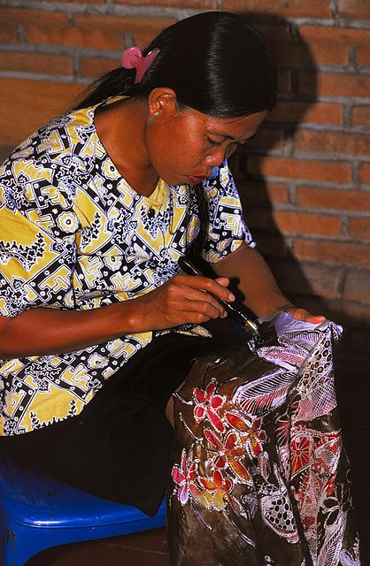 Balinese woman drawing Batik art with a canting needle
