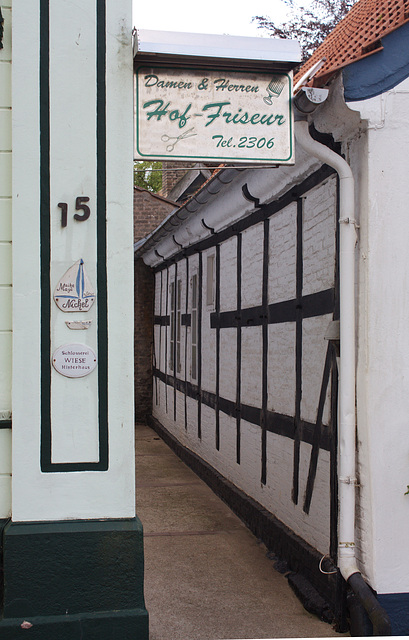 Entrance to a locksmith's shop and a hairdresser in the house at the back