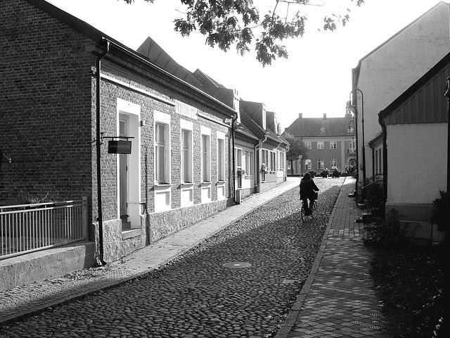 Cycliste sur pavé de cailloux /  Biker on narrow cobblestone street -  Ängelholm, Suède / Sweden.  23 octobre 2008 - N & B