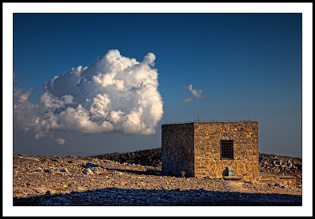 a cloud and a stone hut