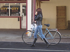 Cycliste en bottes à talons hauts / Walking Swedish biker in jeans & high-heeled boots at her cell phone