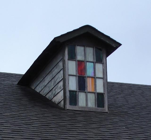 Fenêtre à grenier avec vitre à carreaux colorés / Colorful attic window panes - Hamilton, Alabama. USA - 10 juillet 2010 - Recadrage