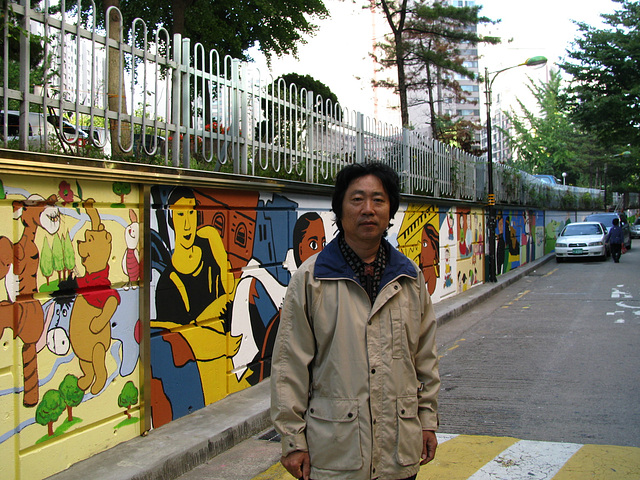 Song stands in front of painted wall=Song Ho staras antaux la pentromuro, 허성-광장동 문화의거리 뮤럴-2009okt.