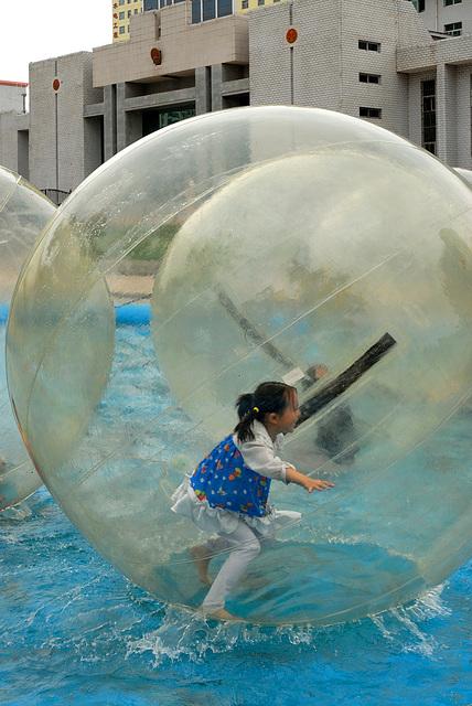 Little girl has fun in a big plastic bulb