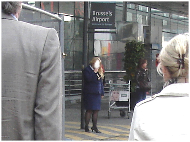 Distant blurry chubby blond flight attendant smoker in high heels  /  Hôtesse de l'air dodue en pause-cigarette - Brussels airport -19-10-2008 - Anonyme