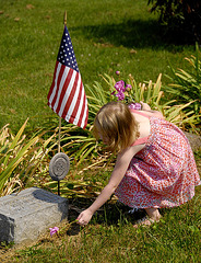 Little Emma, her father active military, places flowers