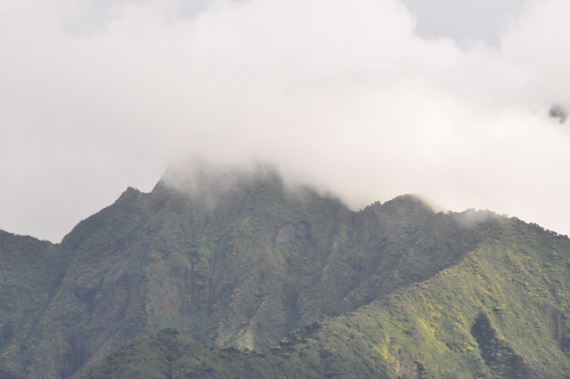 El la turisma bazo videblas impona vulkano, kovrita de nuboj