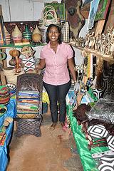 """Vendistino de la Metia Merkato, en Kigali, tenante la """"imigongo""""-aĵon, kiun mi ĵus aĉetis"""