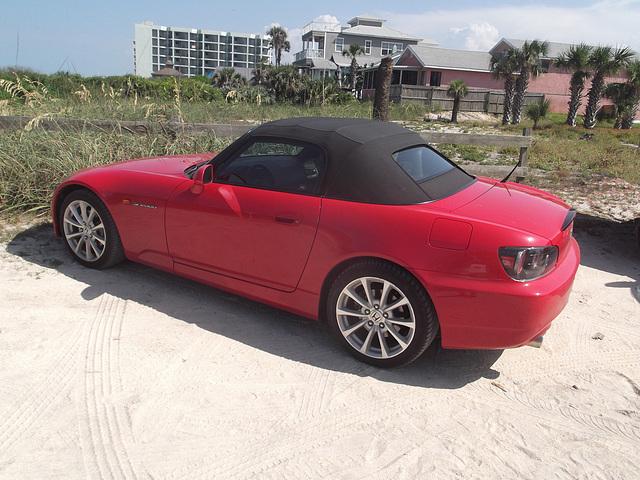 Honda rouge décapotable sur sable / Red convertible Honda on sand.