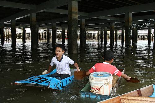 Boys in makeshift boats, Brunei.