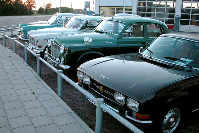 Some old cars in a garage yard