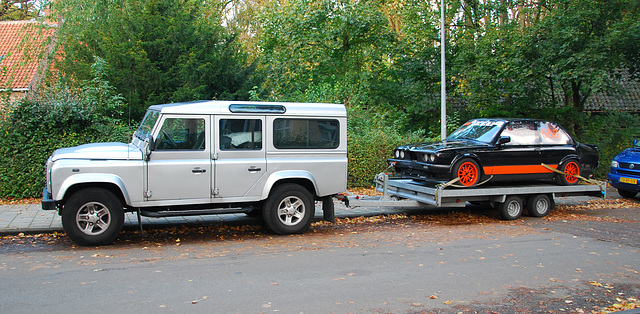 Land Rover with a race BMW on tow
