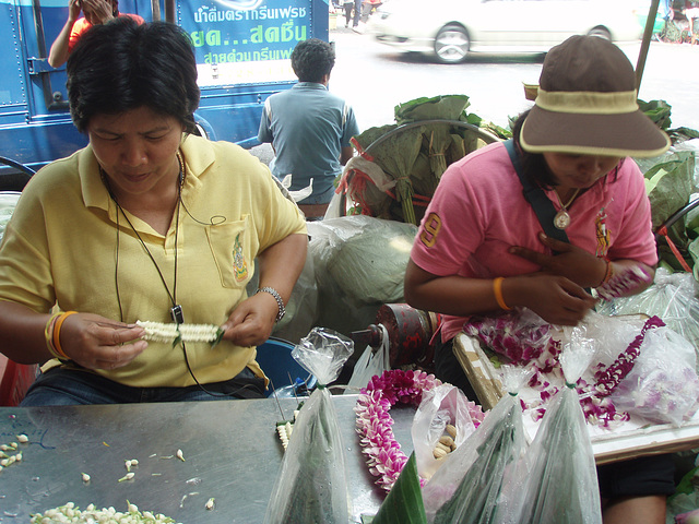 women threading garlands