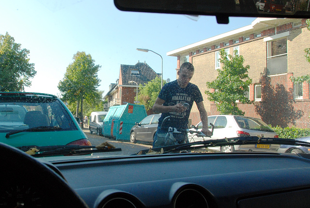Young man making a call in front of my car