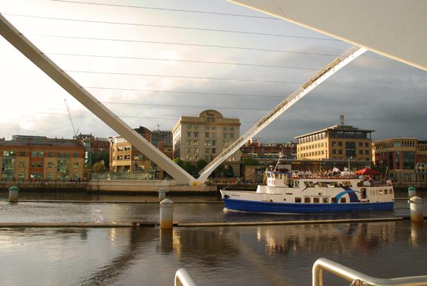 Pleasure boat going under raised Millenium Bridge
