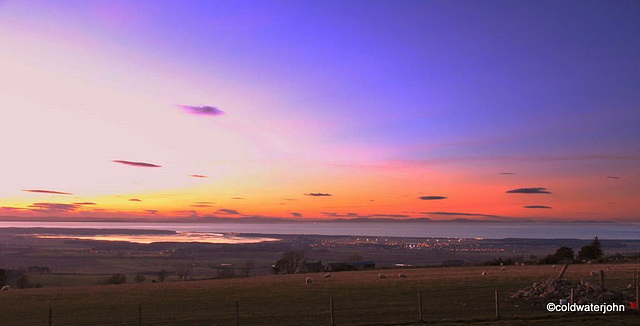 Summer skies and sunset over Findhorn Bay and the Moray Firth, with the lights of Kinloss, from Califer Viewpoint