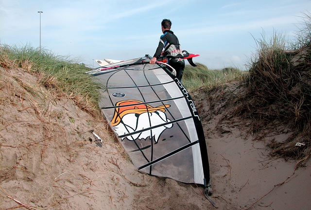 Dragging the wind-surfing board over the dunes