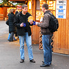 Two young men eating Langos and drinking punsch on the Christmas market