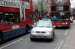 Police car squeezing between two busses on Oxford Street