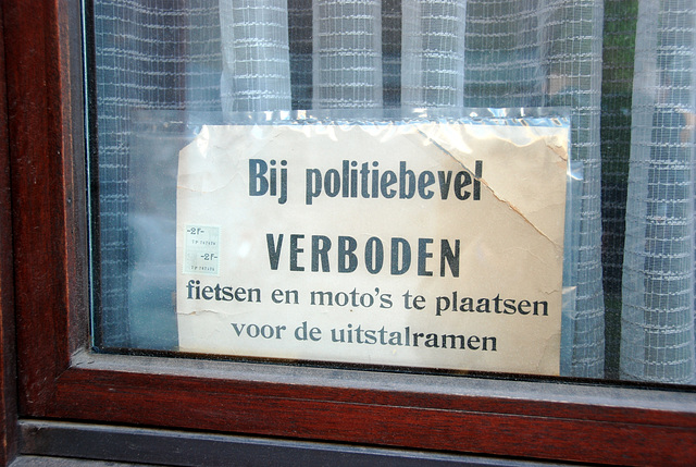 By order of the police it is FORBIDDEN to place bicycles and mopeds in front of the windows