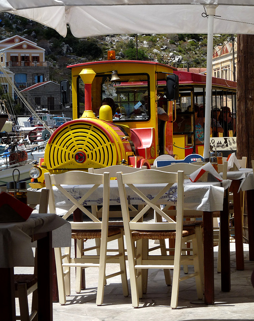 A Bit Close! Tourist Train Passing a Taverna