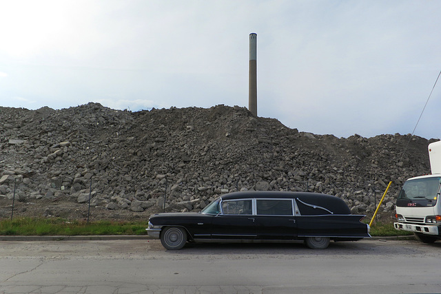 hearse with smoke stack and rubble