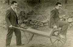 A Man Simultaneously Pushing and Riding a Wheelbarrow