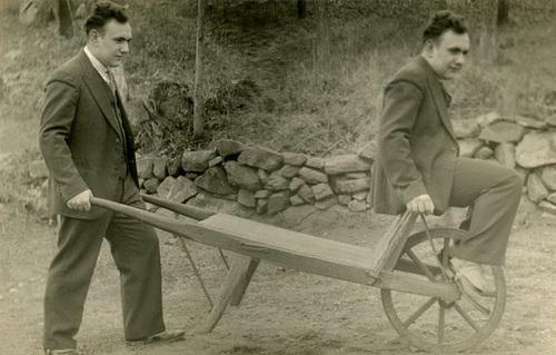 A Man Simultaneously Pushing and Riding a Wheelbarrow