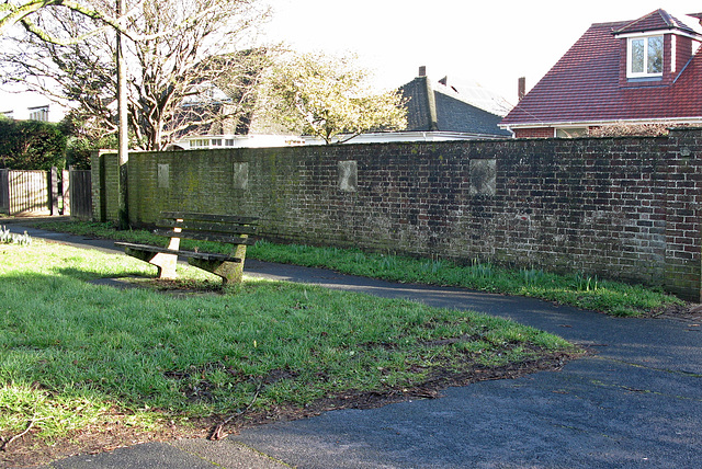 Brick boundary wall and grass verge