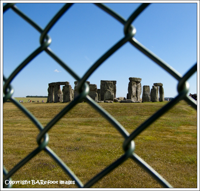 stonehenge through a fence