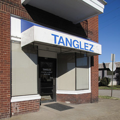 A picture of the noticeable differential between the respective widths of the Tanglez storefront and the Tanglez awning.