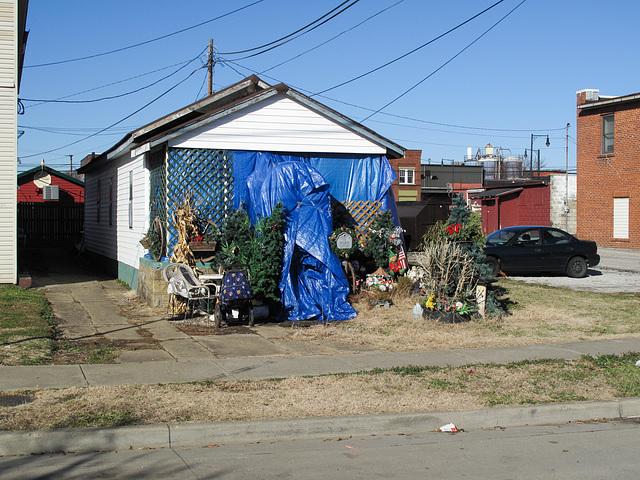 Latticework of porch of tarpaulins; yard decorations.