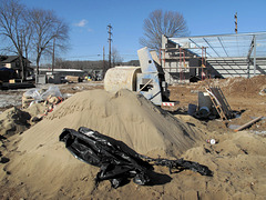 "Sand dune landscape of the construction site of an ""O'Reilly Auto Parts"" biz, across the street from an existing ""Advance Auto Parts"" biz."