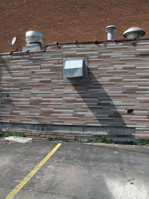 Asphalt sheet siding of strips of fanciful bricklook, with 4 ventilations, 2 available parking spots, a Television Dish.
