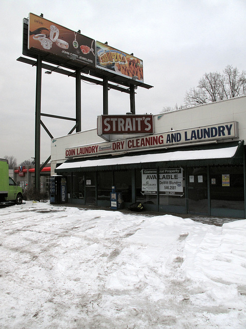 """Grim old grey Strait's, so dreary, w/ respective billboards of jewels & """"Shrimpzilla"""" feast (L-R) in the distant sky."""