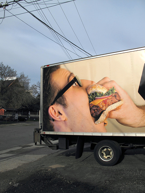 A restaurant ad is printed onto the side of a delivery truck and parked where you'll be sure to see it, because you're the tough sort of fella to whom this kind of male-vs-male cheeseburger imagery ap