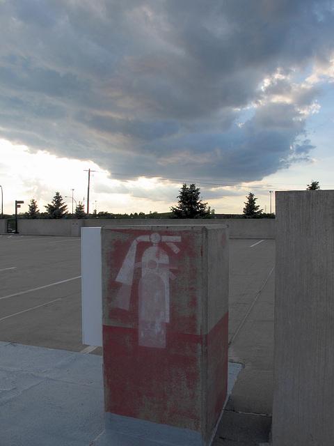 A video of a man standing on the top level of a parking structure, frantically spraying a fire extinguisher at an approaching bank of clouds.