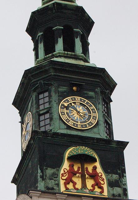 Urbodoma tureto kun bela horloĝo kaj leonparo sub arbo. (Rathaustürmchen mit schöner Uhr und Löwenpaar unter einem Baum.)