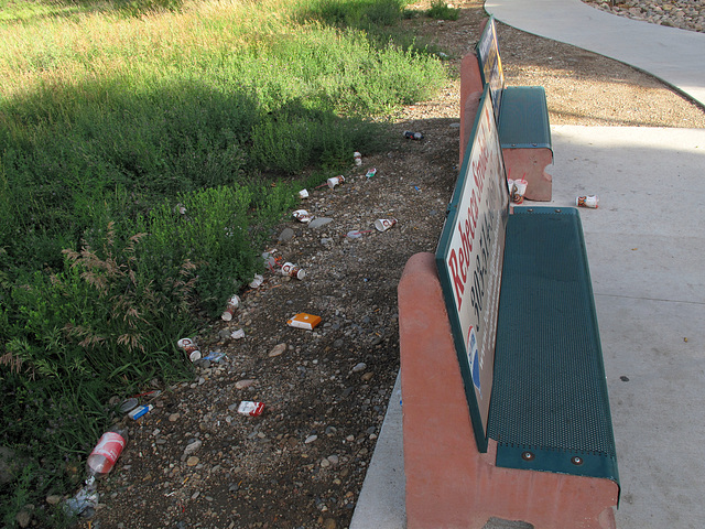 Trash thrown over shoulders at bus stop benches in Golden, Colorado.