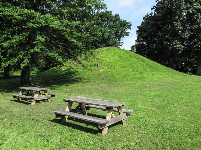Rising elegance of mound-shaped earthwork of the vast Pre-Columbian Age.  Kept mowed, w/ two chairs.
